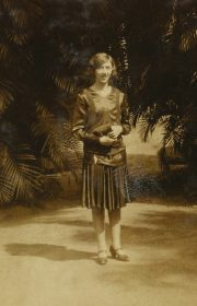 Rio de Janeiro, 1929: Alice has stylish short hair and wears a drop waist dress with pleated skirt.